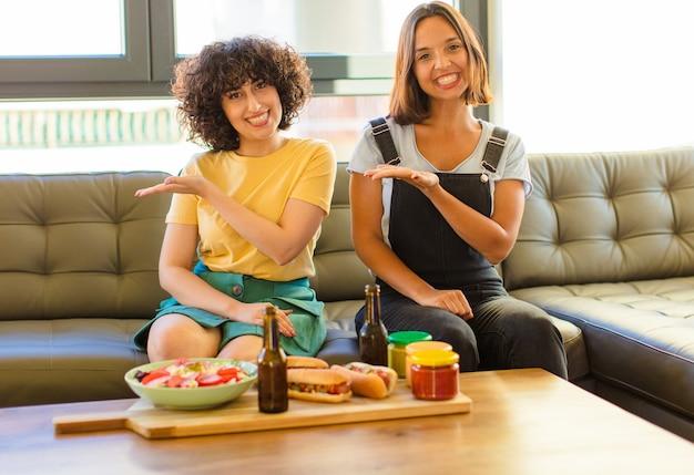 元気に笑って、幸せを感じて、手のひらでコピースペースでコンセプトを示す若いきれいな女性