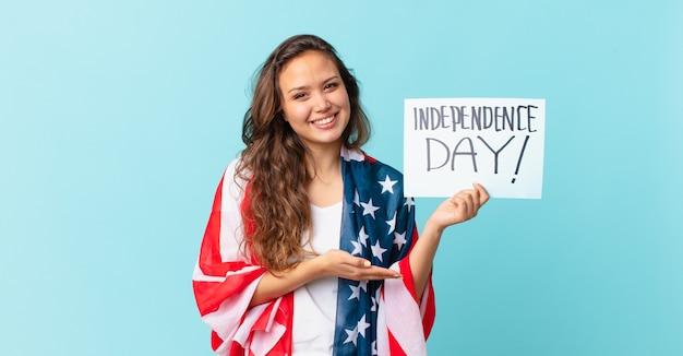 Молодая красивая женщина весело улыбается, чувствует себя счастливой и демонстрирует концепцию дня независимости