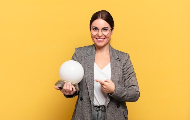 Young pretty woman smiling cheerfully, feeling happy and pointing to the side and upwards, showing object in copy space