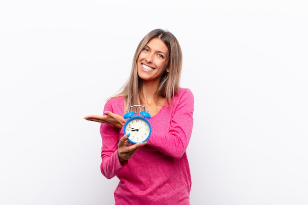 Young pretty woman smiling cheerfully, feeling happy and showing a concept in copy space with palm of hand holding an alarm clock.