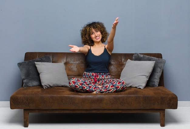 Молодая красивая женщина, весело, давая теплые, дружелюбные, любящие приветственные объятия, чувствуя себя счастливым и очаровательны, сидя на диване.