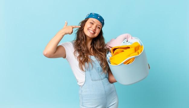 自信を持って笑顔の若いきれいな女性は、自分の広い笑顔を指して、洗濯かごを持っています