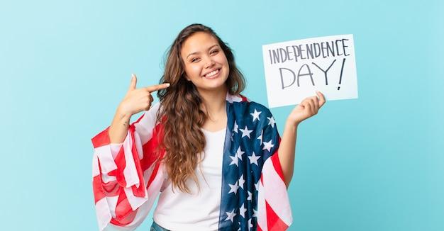 自信を持って笑顔の若いきれいな女性は、自分の広い笑顔の独立記念日のコンセプトを指しています
