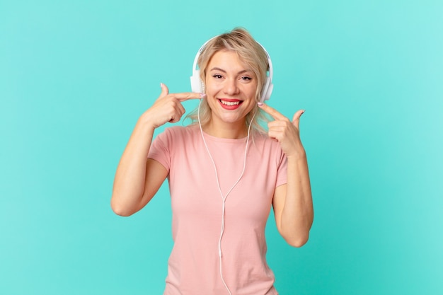 若いきれいな女性が自信を持って微笑み、自分の広い笑顔を指しています。音楽のコンセプトを聞く