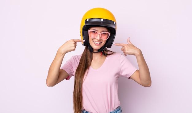 자신의 넓은 미소를 자신있게 가리키는 웃는 젊은 예쁜 여자. 오토바이 라이더와 헬멧