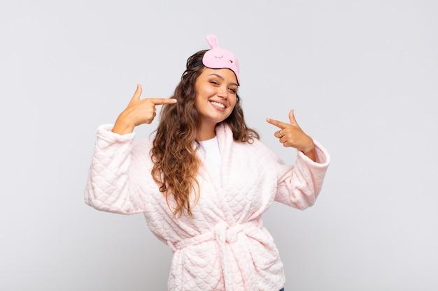 Молодая красивая женщина, уверенно улыбаясь, указывая на собственную широкую улыбку, позитивное, расслабленное, довольное отношение в пижаме
