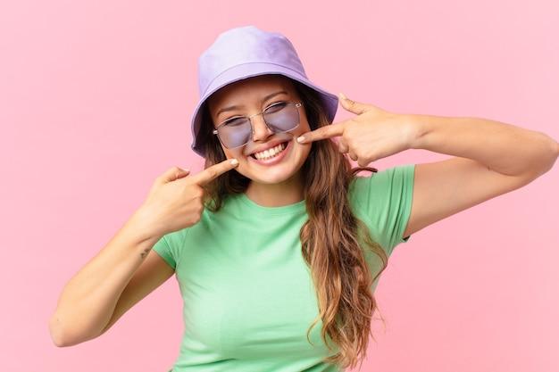 自信を持って笑顔の若いきれいな女性は、自分の広い笑顔を指しています。夏のコンセプト