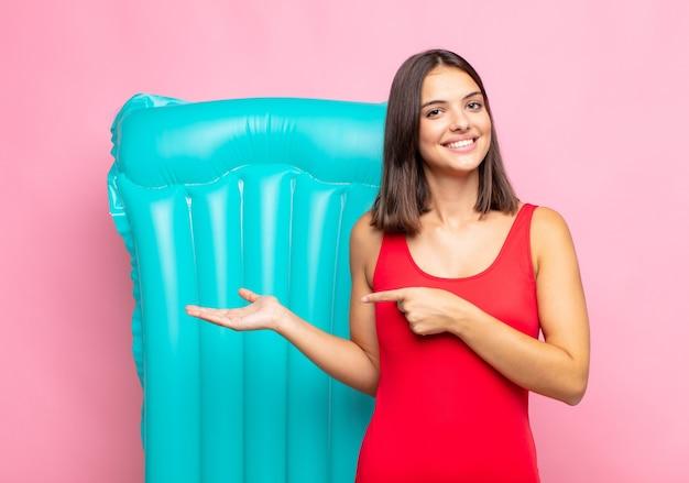 젊은 예쁜 여자 웃고, 행복하고 평온하고 만족스럽고, 개념이나 아이디어를 가리키는 복사 공간 측면