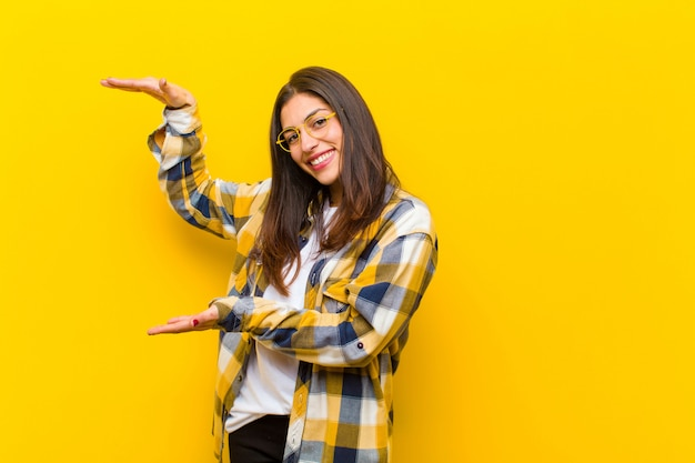Young  pretty woman smiling, feeling happy, positive and satisfied, holding or showing object or concept on copy space against orange wall