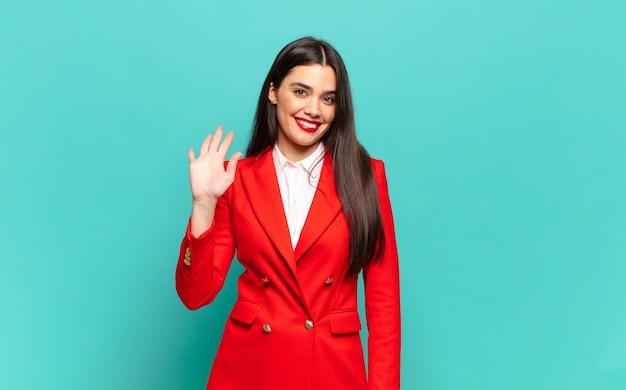 幸せで元気に笑って、手を振って、あなたを歓迎して挨拶するか、さようならを言う若いきれいな女性。ビジネスコンセプト