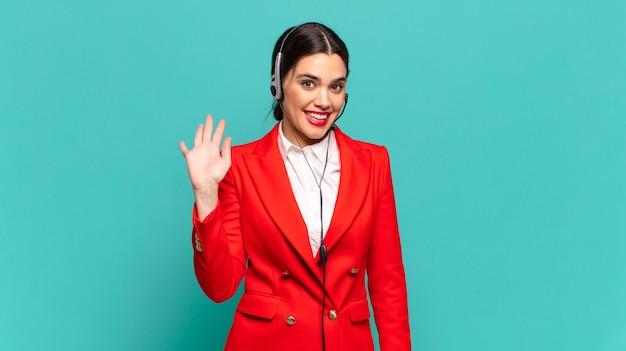 Молодая красивая женщина счастливо и весело улыбается, машет рукой, приветствует и приветствует вас или прощается. концепция телемаркетинга