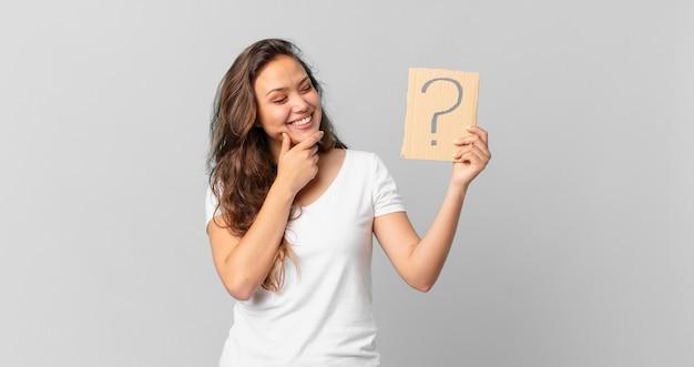 젊고 예쁜 여자가 행복하게 웃고 공상을 하거나 의심하고 물음표 기호를 들고 있다