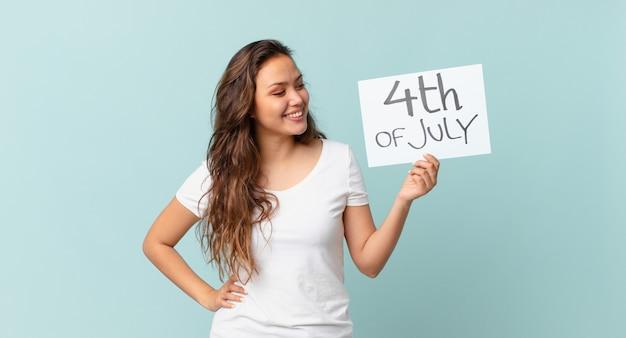 幸せに笑って、空想にふけるか、独立記念日の概念を疑う若いきれいな女性
