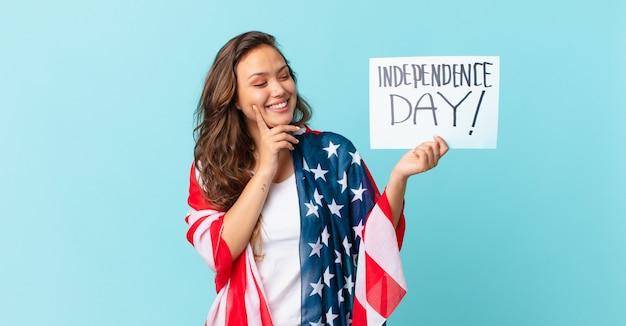Молодая красивая женщина счастливо улыбается и мечтает или сомневается в концепции дня независимости
