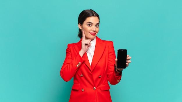 Молодая красивая женщина счастливо улыбается и мечтает или сомневается, глядя в сторону. концепция смартфона