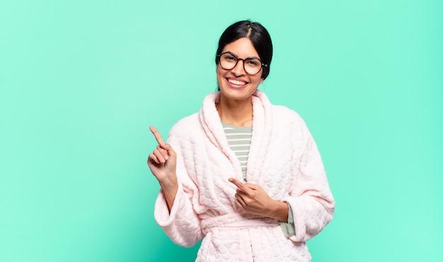 幸せそうに笑って、コピースペースでオブジェクトを示す両手で横と上を指している若いきれいな女性。パジャマのコンセプト