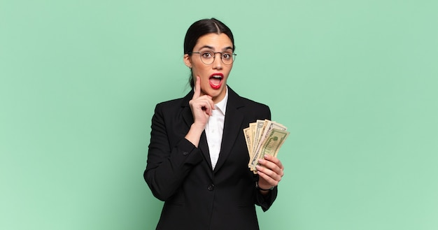 Young pretty woman smiling happily and daydreaming or doubting, looking to the side. business and banknotes concept