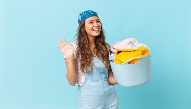 幸せに笑って、手を振って、あなたを歓迎して挨拶し、洗濯かごを持っている若いきれいな女性