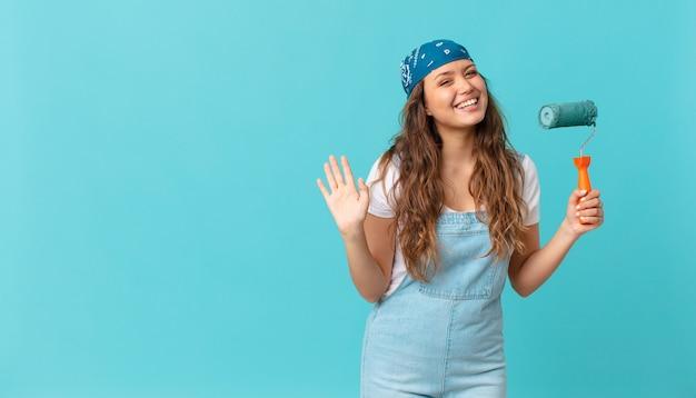 幸せに笑って、手を振って、あなたを歓迎して挨拶し、壁を描く若いきれいな女性