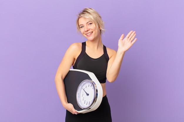젊고 예쁜 여자가 행복하게 웃고, 손을 흔들고, 환영하고 인사합니다. 다이어트 개념
