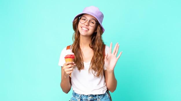 젊고 예쁜 여자가 행복하게 웃고, 손을 흔들고, 아이스크림을 들고 환영하고 인사합니다. 여름 개념