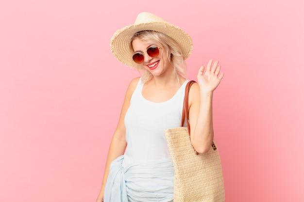 幸せに笑って、手を振って、あなたを歓迎し、挨拶する若いきれいな女性。夏の観光コンセプト