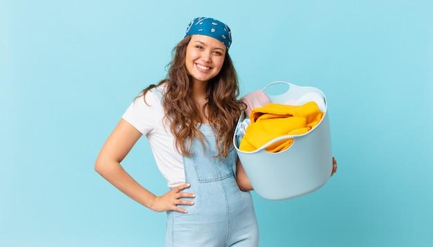 腰に手を当てて幸せそうに笑って自信を持って、洗濯かごを持っている若いきれいな女性