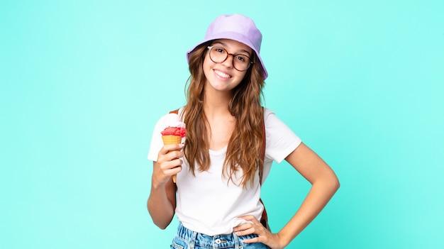 腰に手を当てて幸せそうに笑って、アイスクリームを持って自信を持って若いきれいな女性。夏のコンセプト