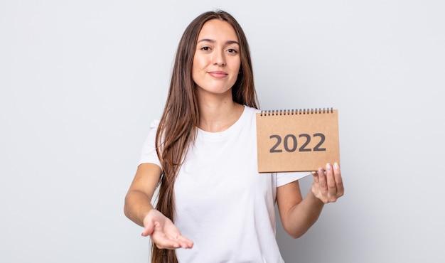 Молодая красивая женщина счастливо улыбается с дружелюбными и предлагает и показывает концепцию. концепция планировщика 2022 года