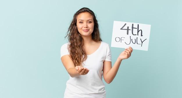 フレンドリーで幸せに笑って、コンセプト独立記念日のコンセプトを提供し、示す若いきれいな女性