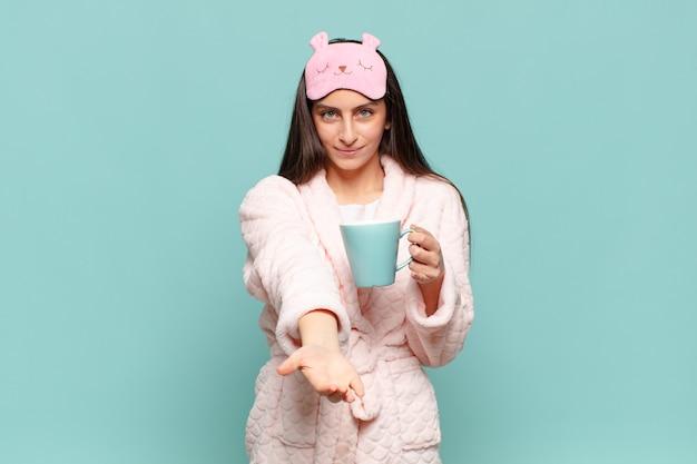 フレンドリーで自信に満ちた前向きな表情で幸せそうに笑っている若いきれいな女性は、オブジェクトやコンセプトを提供し、示しています。パジャマのコンセプトを身に着けて目を覚ます