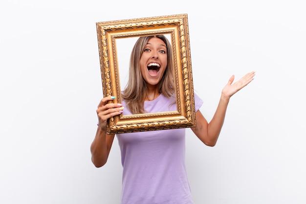 Молодая красивая женщина счастливо улыбается с дружелюбным, уверенным, позитивным взглядом, предлагая и показывая объект или концепцию с рамкой в стиле барокко.