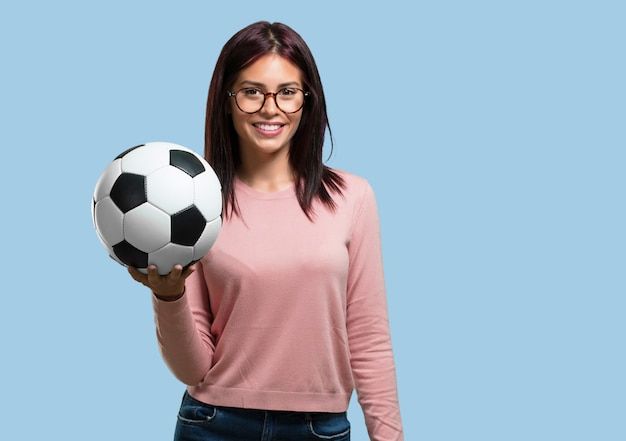 Young pretty woman smiling and happy, holding a soccer ball, competitive attitude