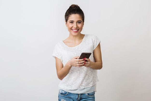 Молодая красивая женщина улыбается в белой футболке, держа и используя смартфон, мобильное устройство, изолированные