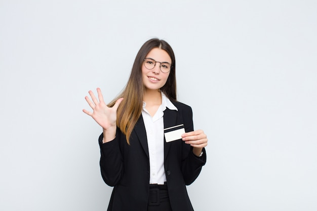 Young pretty woman smiling and looking friendly, showing number five or fifth with hand forward, counting down with a credit card