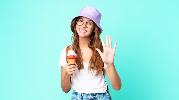 Young pretty woman smiling and looking friendly, showing number five holding an ice cream. summer concept