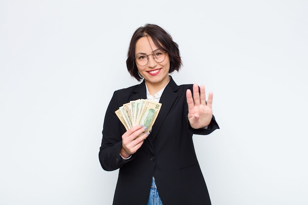 Young pretty woman smiling and looking friendly, showing number four or fourth with hand forward, counting down with bills