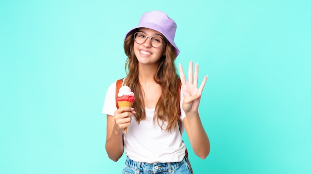 Young pretty woman smiling and looking friendly, showing number four holding an ice cream. summer concept