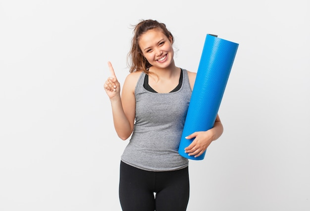 Young pretty woman smiling and looking friendly, showing number one and holding a yoga mat