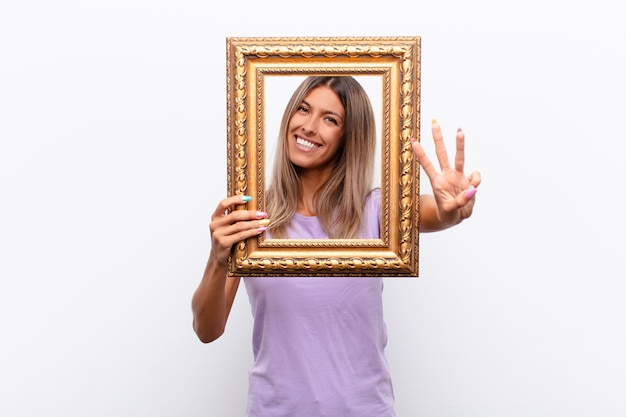 Young pretty woman smiling and looking friendly, showing number two or second with hand forward, counting down with a baroque frame.