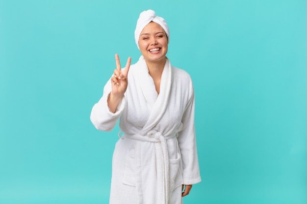 Young pretty woman smiling and looking friendly, showing number two and wearing bath robe after shower