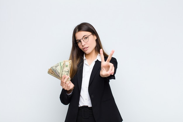 Young pretty woman smiling and looking happy, carefree and positive, gesturing victory or peace with one hand with banknotes