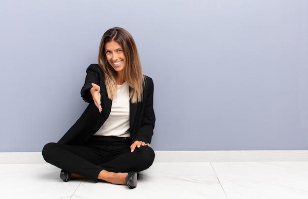 若いきれいな女性の笑顔、幸せ、自信を持って、フレンドリーで探して、ハンドシェイクを提供して、ビジネスコンセプトに協力して、契約を結ぶ