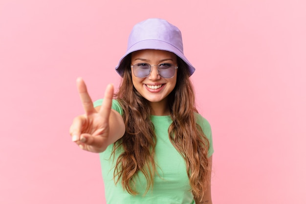 Young pretty woman smiling and looking happy, gesturing victory or peace. summer concept