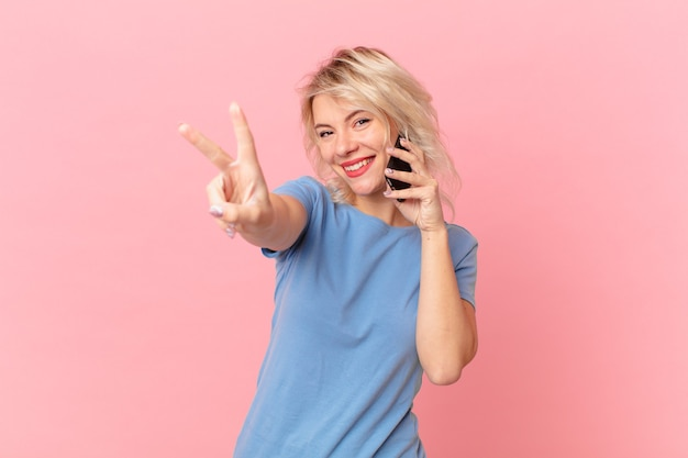 Young pretty woman smiling and looking happy, gesturing victory or peace