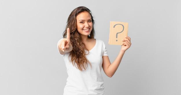 젊고 예쁜 여자가 자랑스럽게 웃고 자신있게 1위를 하고 물음표 기호를 들고 있다