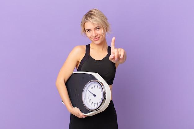 젊고 예쁜 여성이 자랑스럽게 웃고 자신있게 1위를 만들고 있습니다. 다이어트 개념