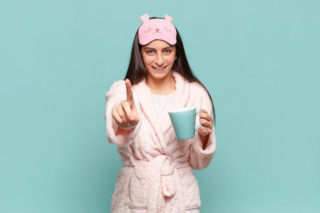 誇らしげに自信を持って笑顔でナンバーワンのポーズをとる若いきれいな女性は、リーダーのように感じます。パジャマのコンセプトを身に着けて目を覚ます