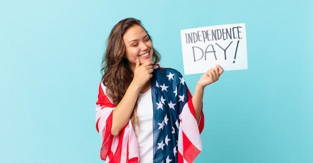 Молодая красивая женщина улыбается со счастливым, уверенным выражением лица, положив руку на подбородок концепции дня независимости