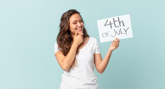 Молодая красивая женщина улыбается со счастливым, уверенным выражением лица с рукой на концепции дня независимости подбородка